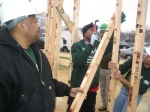 YouthBuild instructors lend support as students nail the frame together