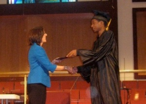 Graduate Steven Turner recieves his diploma from Board Chair Cindy Skinner