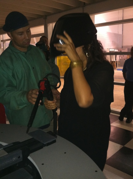 Executive Director Simran Sidhu tries out the welding simulator - an efficient way for students to learn technique without using up materials. The machine offers detailed feedback and hints to students to help them improve.